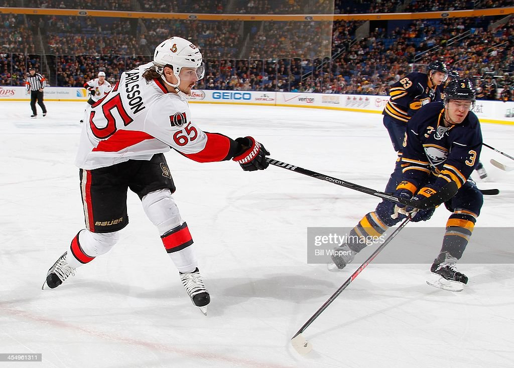 Erik Karlsson #65 of the Ottawa Senators shoots the puck past Mark Pysyk #3 of the Buffalo Sabres on December 10, 2013 at the First Niagara Center in Buffalo, New York.
