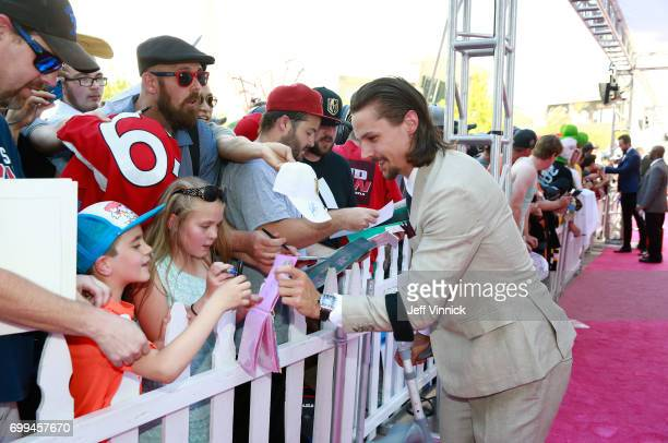 Erik Karlsson of the Ottawa Senators signs an autograph as he arrives on the magenta carpet for the 2017 NHL Awards at TMobile Arena on June 21 2017...
