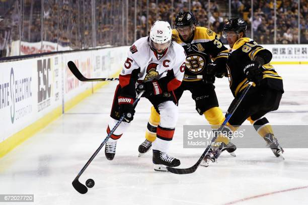 Erik Karlsson of the Ottawa Senators skates against David Pastrnak and Patrice Bergeron of the Boston Bruins during overtime in Game Six of the...