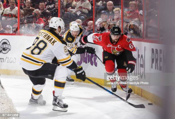 Erik Karlsson of the Ottawa Senators skates for the puck against David Pastrnak and Riley Nash of the Boston Bruins in Game Five of the Eastern...