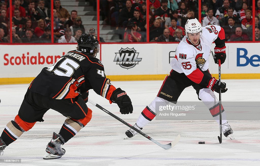 Erik Karlsson of the Ottawa Senators skates up ice with the puck against Sami Vatanen #45 of the Anaheim Ducks at Canadian Tire Centre on October 25, 2013 in Ottawa, Ontario, Canada.