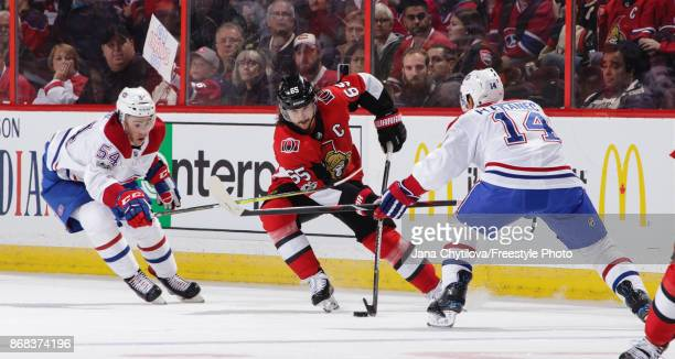 Erik Karlsson of the Ottawa Senators skates with the puck splitting between Charles Hudon and Tomas Plekanec of the Montreal Canadiens in the second...