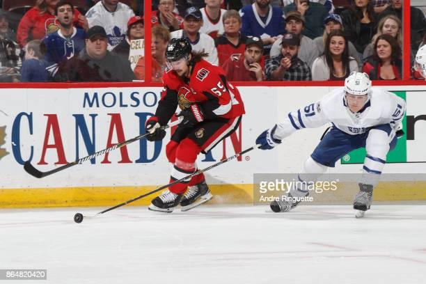 Erik Karlsson of the Ottawa Senators stickhandles the puck against Jake Gardiner of the Toronto Maple Leafs at Canadian Tire Centre on October 21...
