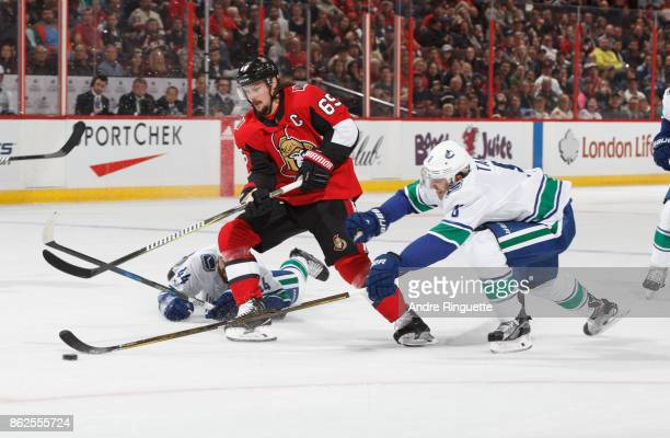 Erik Karlsson of the Ottawa Senators stickhandles the puck between Erik Gudbranson and Christopher Tanev of the Vancouver Canucks on a power play at...