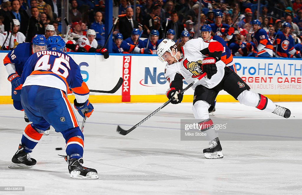 Erik Karlsson #65 of the Ottawa Senators takes a shot while being defended by Matt Donovan #46 of the New York Islanders at Nassau Veterans Memorial Coliseum on April 8, 2014 in Uniondale, New York.