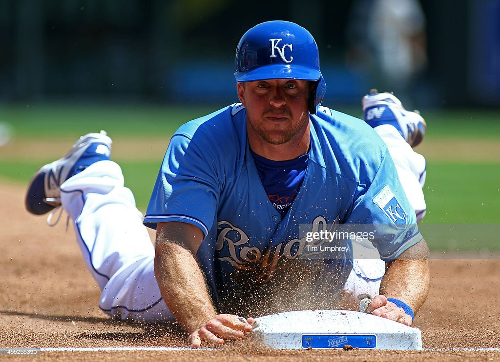 Erik Kratz of the Kansas City Royals slides into third base in the third inning of a game against the Oakland Athletics at Kauffman Stadium on August...