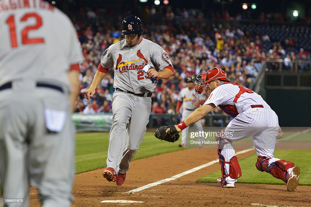 Erik Kratz #31 of the Philadelphia Phillies is unable to get the tag on <a gi-track='captionPersonalityLinkClicked' href=/galleries/search?phrase=David+Freese+-+Jogador+de+basebol&family=editorial&specificpeople=4948315 ng-click='$event.stopPropagation()'>David Freese</a> #23 of the St. Louis Cardinals as he scores a run in the seventh inning and teammate <a gi-track='captionPersonalityLinkClicked' href=/galleries/search?phrase=Ty+Wigginton&family=editorial&specificpeople=211533 ng-click='$event.stopPropagation()'>Ty Wigginton</a> #12 watches at Citizens Bank Park on April 18, 2013 in Philadelphia, Pennsylvania. The Cardinals won 4-3.