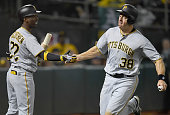 Erik Kratz of the Pittsburgh Pirate is congratulated by Andrew McCutchen after Kratz scored against the Oakland Athletics in the top of the tenth...