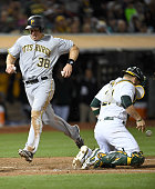 Erik Kratz of the Pittsburgh Pirates scores running past Stephen Vogt of the Oakland Athletics in the top of the tenth inning at Oco Coliseum on July...