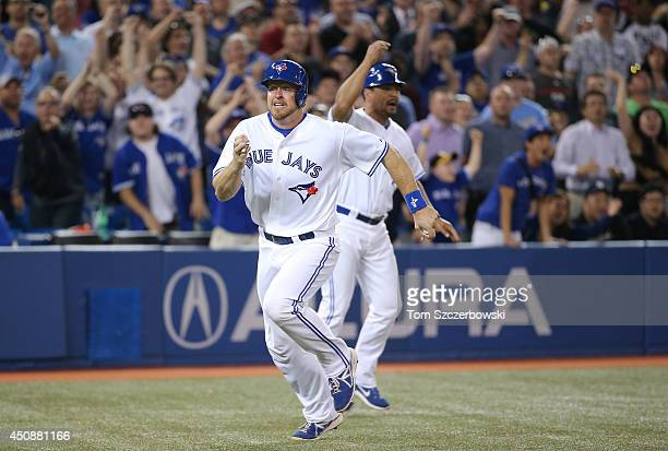 Erik Kratz of the Toronto Blue Jays comes around third base and heads home to score the gamewinning run in the ninth inning during an MLB game...