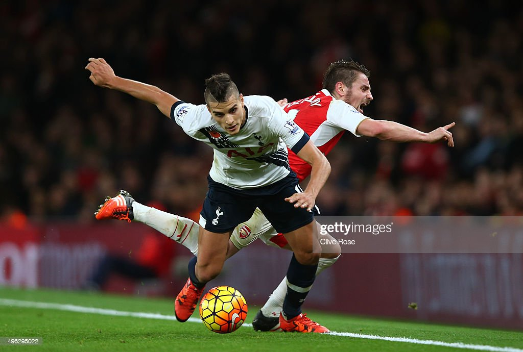 Erik Lamela of Spurs holds off Mathieu Debuchy of Arsenal during the Barclays Premier League match between Arsenal and Tottenham Hotspur at the...