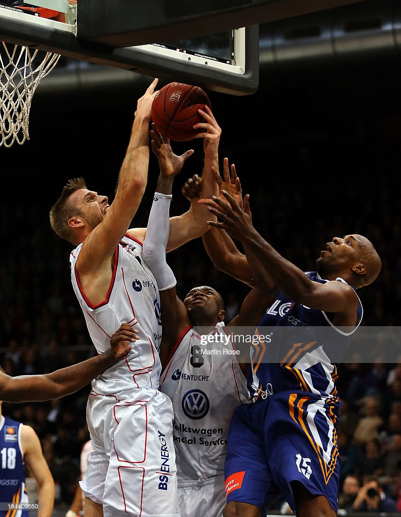 Erik Land and Harding Nana of Braunschweig and Derrick Allen of Bremerhaven compete for the ball during the Beko Basketball Bundesliga match between...