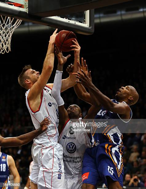 Erik Land and Harding Nana of Braunschweig and Derrick Allen of Bremerhaven compete for the ball during the Beko Basketball Bundesliga match between...