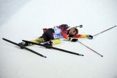 Erik Lesser of Germany collapses on the snow after competing in the Men's Sprint 10 km during day one of the Sochi 2014 Winter Olympics at Laura...
