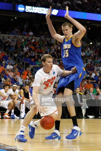 Erik Murphy of the Florida Gators drives against Greg Somogyi of the UC Santa Barbara Gauchos during the second round of the 2011 NCAA men's...
