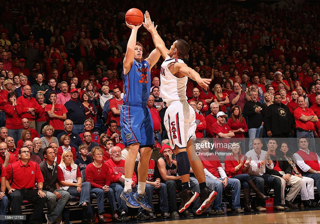 Erik Murphy #33 of the Florida Gators puts up a three point shot over Nick Johnson #13 of the Arizona Wildcats during the college basketball game at McKale Center on December 15, 2012 in Tucson, Arizona. The Wildcats defeated the Gators 65-64.