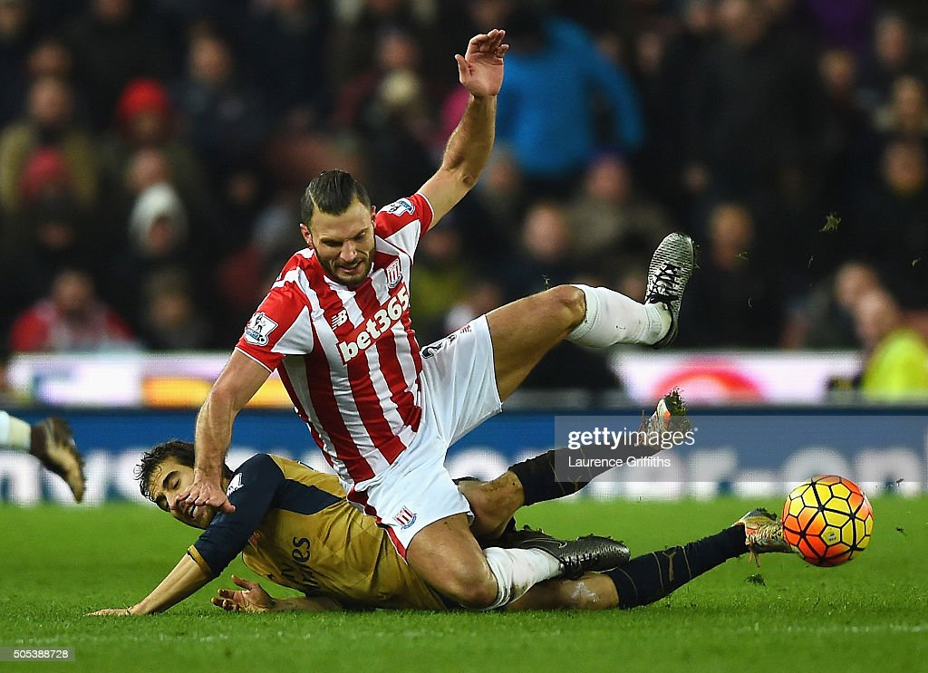 Erik Pieters of Stoke City is tackled by Mathieu Flamini of Arsenal during the Barclays Premier League match between Stoke City and Arsenal at Britannia Stadium on January 17, 2016 in Stoke on Trent, England.
