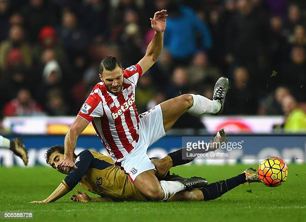 Erik Pieters of Stoke City is tackled by Mathieu Flamini of Arsenal during the Barclays Premier League match between Stoke City and Arsenal at...