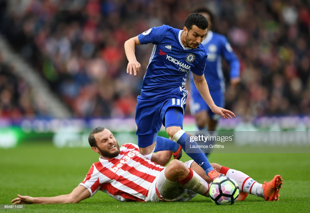 Erik Pieters of Stoke City (L) tackles Pedro of Chelsea (R) during the Premier League match between Stoke City and Chelsea at Bet365 Stadium on March 18, 2017 in Stoke on Trent, England.