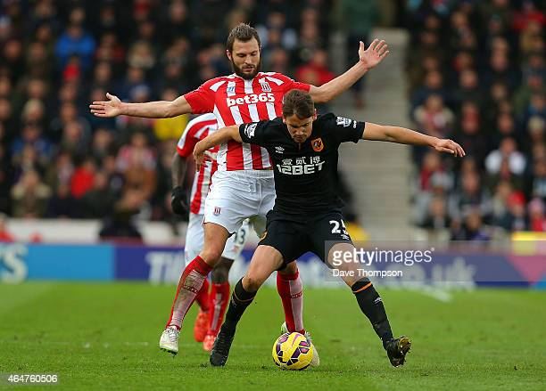 Erik Pieters of Stoke City tangles with Gaston Ramirez of Hull City during the Barclays Premier League match between Stoke City and Hull City at...