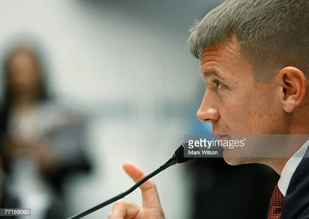 Erik Prince chairman of the Prince Group LLC and Blackwater USA holds up a picture showing the affect of a car bomb while testifying during a House...