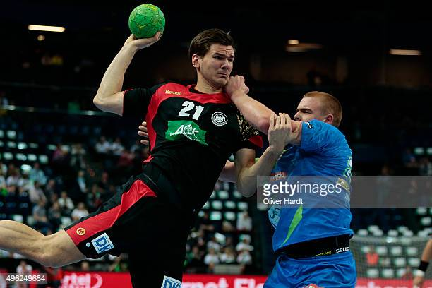 Erik Schmidt of Germany challenges for the ball with Matej Gaber of Slovenia during the Handball Supercup between Germany and Slovenia on November 8...