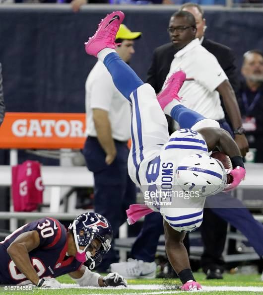 Erik Swoope of the Indianapolis Colts is tripped up by Kevin Johnson of the Houston Texans in the fourth quarter during the NFL game between the...