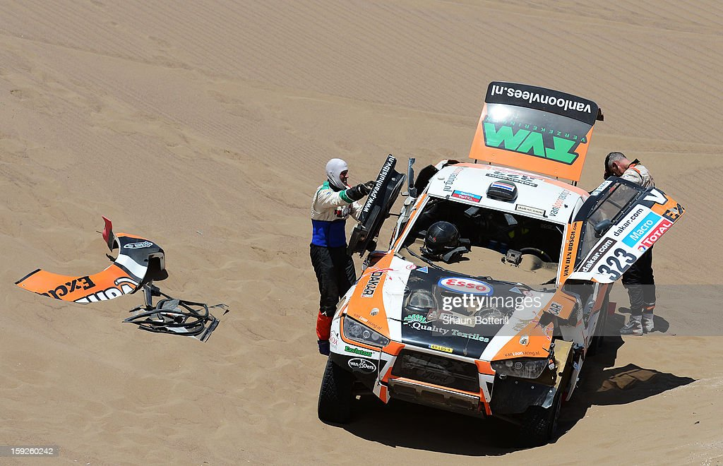 Erik Van Loon and co-driver Marc Wams of team HRX inspect their car after crashing during stage 6 from Arica to Calama during the 2013 Dakar Rally on January 10, 2013 in Arica, Chile.