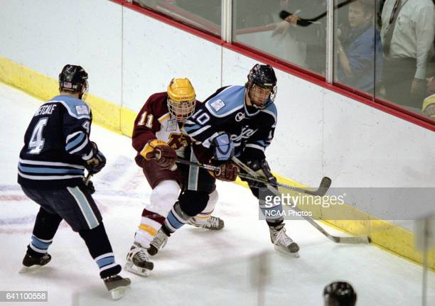 Erik Wendell of Minnesota fights his way through Robert Liscak and Peter Metcalf of the University of Maine during the Division 1 Men's Hockey...
