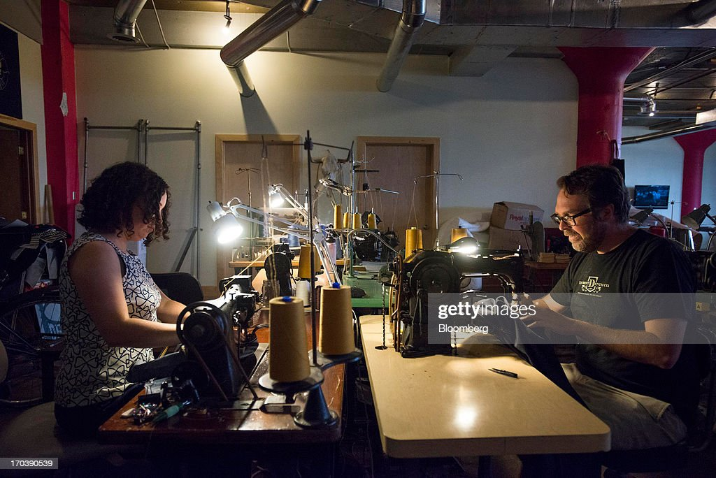 Erik Yelsma, owner of Detroit Denim, right, and an employee work on sewing machines inside Detroit Denim, in Detroit, Michigan, U.S., on Wednesday, June 12, 2013. The Commerce Department is scheduled to release monthly business inventories data on June 13. Photographer: Ty Wright/Bloomberg via Getty Images