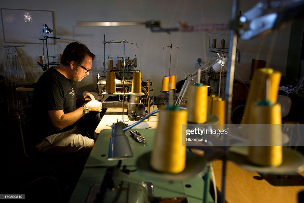 Erik Yelsma, owner of Detroit Denim, sews belt loops onto a pair of Denim Jeans at Detroit Denim, in Detroit, Michigan, U.S., on Wednesday, June 12, 2013. The Commerce Department is scheduled to release monthly business inventories data on June 13. Photographer: Ty Wright/Bloomberg via Getty Images