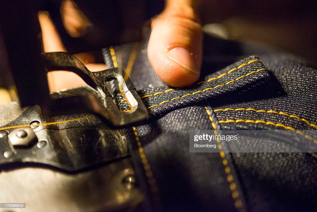 Erik Yelsma, owner of Detroit Denim, sews belt loops onto a pair of Denim Jeans at Detroit Denim, in Detroit, Michigan, U.S.,, U.S., on Wednesday, June 12, 2013. The Commerce Department is scheduled to release monthly business inventories data on June 13. Photographer: Ty Wright/Bloomberg via Getty Images
