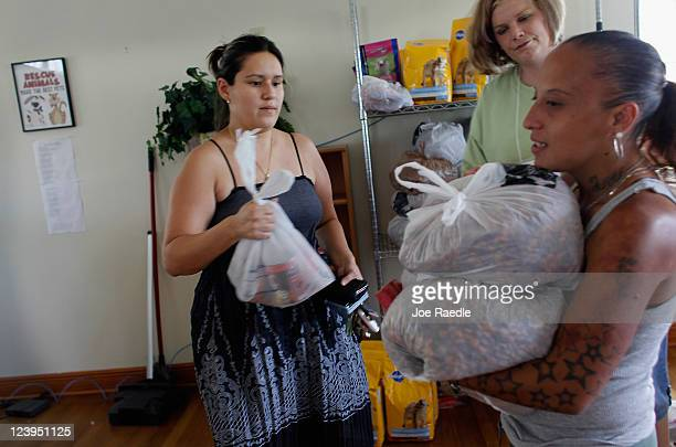 Erika Astudillo and Veronica Cruz get bags of dog food from Shannon Patrick at Fido's Food Bank at the Peggy Adams Animal Rescue League on September...