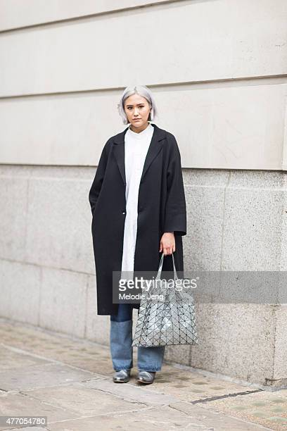 Erika Bowes wears a COS jacket Other Stories top Cheap Monday jeans Topshop shoes and an Issey Miyake bag during The London Collections Men SS16 at...