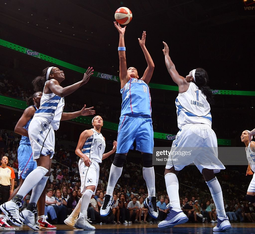Erika de Souza of the Atlanta Dream shoots against Nakia Sanford and Crystal Langhorne of the Washington Mystics during Game One of the 2010 WNBA...