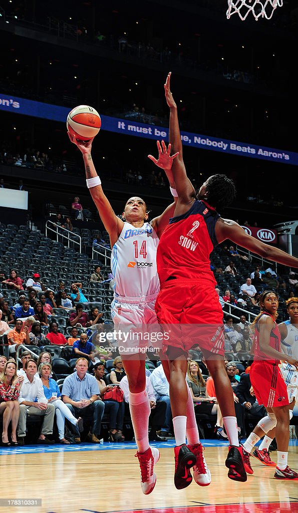 Erika deSouza #14 of the Atlanta Dream puts up a shot against <a gi-track='captionPersonalityLinkClicked' href=/galleries/search?phrase=Michelle+Snow&family=editorial&specificpeople=208195 ng-click='$event.stopPropagation()'>Michelle Snow</a> #2 of the Washington Mystics at Philips Arena on August 28 2013 in Atlanta, Georgia.