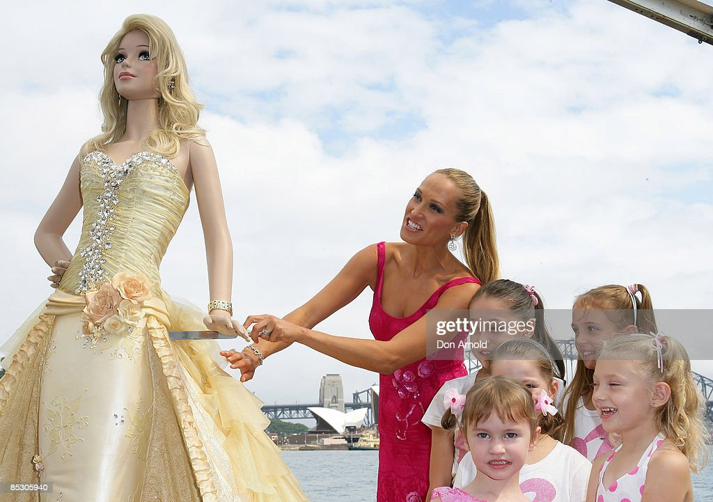 Erika Heynatz standing alongside children poses with a lifesize Barbie birthday cake wearing an Alex Perry dress to celebrate the 50th anniversary of...