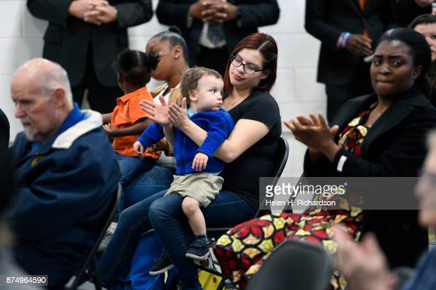 DENVER CO NOVEMBER 15 Erika Sanchez holding her 2 year old son Daniel Lamas listens during a press conference officially opening a new homeless...