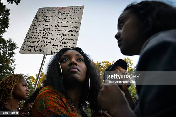 Erika Totten L holds a sign listing names of people killed by police as hundreds of people gather at Meridian Hill Park for a peaceful vigil and...