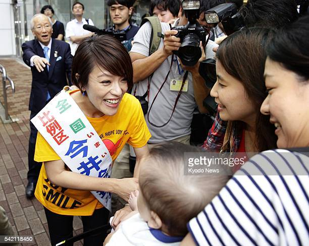 Eriko Imai a member of the female Jpop group SPEED shakes hands with people after giving her first stump speech in Tokyo's Yurakucho district on June...