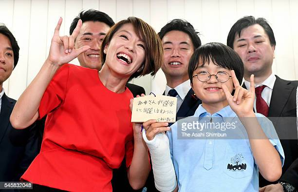 Eriko Imai of the Liberal Democratic Party celebrates winning a seat in the Upper House eelction with her son at her election campaign headquarters...