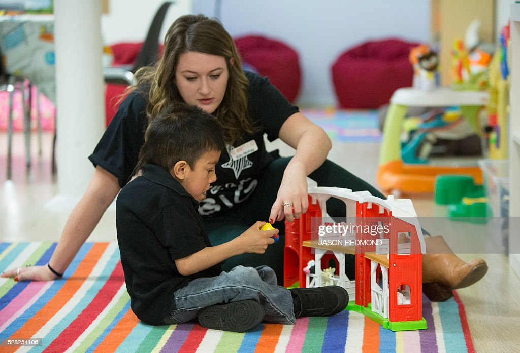 Erin McKay, of the non profit Mary's Place, plays wth Gio Caro, 6, who is staying with his mom at a building Amazon owns and offered as a temporary shelter for women and their families in Seattle, Washington on May 4, 2016. According to the non profit, Marys Place is a temporary emergency family nightshelter housing up to 60 families each night, including pets. Mary's place helps homeless women, children and families to reclaim their lives by providing shelter, nourishment, resources, healing and hope in a safe community. / AFP / Jason Redmond