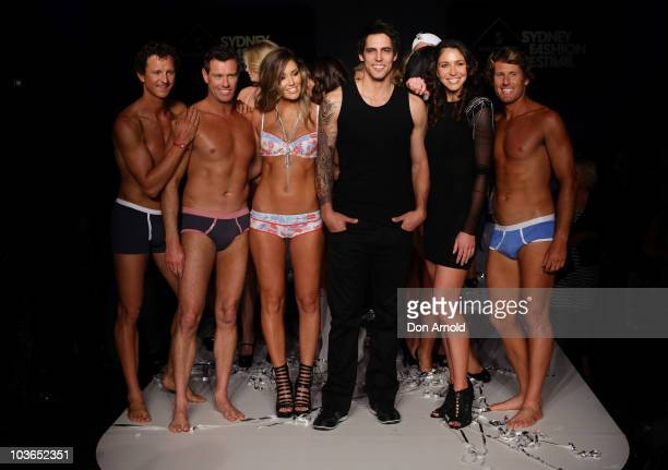 Erin McNaught Mitchell Johnson and Giann Rooney pose alongside models on the catwalk during the Hot In The City Intimates group show as part of...