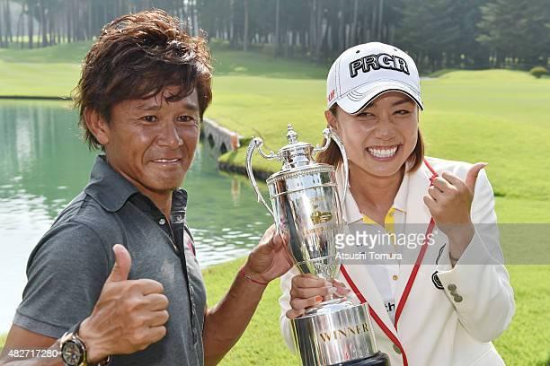 Erina Hara of Japan and her caddie Takashi Hoshina pose with the trophy after winning the Daito Kentaku Eheyanet Ladies 2015 at the Narusawa Golf...