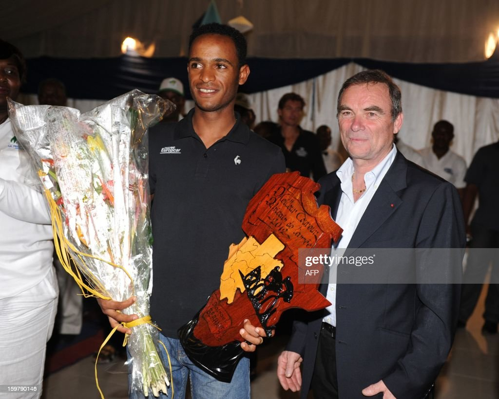 Eritrean Natnael Berhane poses as he receives the African Cyclist of the year 2012 trophy from French Bernard Hinault, five-times Tour de France champion, at the Beach Club in Libreville, on January 20, 2013 after the seventh and last 126 kms stage of the eighth edition of the Tropicale Amissa Bongo cycling race between Owendo and Libreville in Gabon. The award established this year for the first time by the organizers of Tropicale Amissa Bongo rewards African cyclist who made the strongest impact during the season of events including on the African continent.