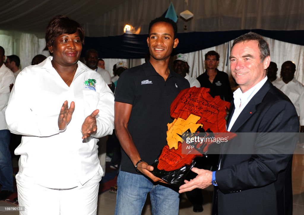 Eritrean Natnael Berhane (C) receives the African Cyclist of the year 2012 trophy from French Bernard Hinault (R), five-times Tour de France champion, at the Beach Club in Libreville, on January 20, 2013 after the seventh and last 126 kms stage of the eighth edition of the Tropicale Amissa Bongo cycling race between Owendo and Libreville in Gabon. The award established this year for the first time by the organizers of Tropicale Amissa Bongo rewards African cyclist who made the strongest impact during the season of events including on the African continent. AFP PHOTO / STEVE JORDAN