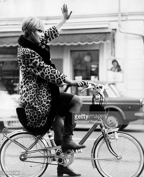 Eritreanborn Italian singer and producer Lara Saint Paul pedalling in the saddle of a bicycle raising her arm 1960s