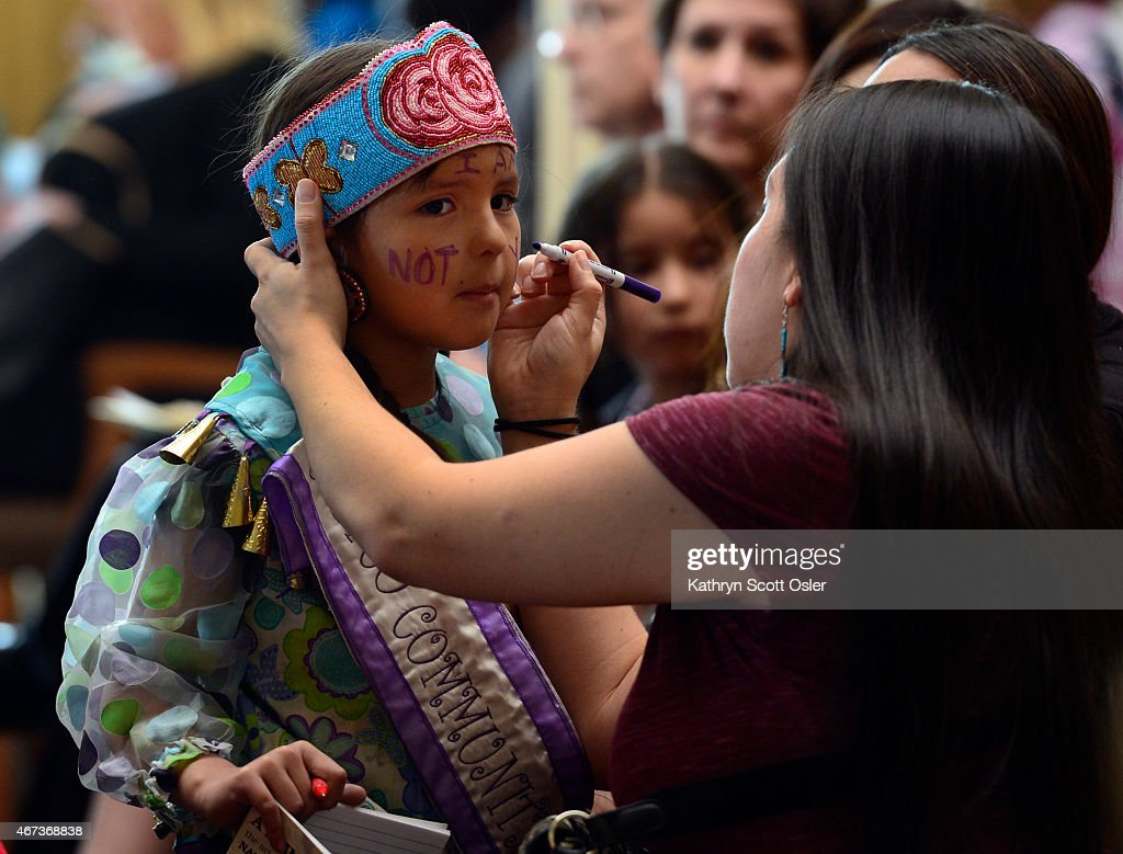 Erlidawn Roy representing the Meskwaki Ojibwe Laguna Pueblo and the Isleta Pueblo tribes writes a message 'I am not your mascot' on the face of...
