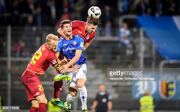 Ermin Bicakcic of Hoffenheim challenges AntonioMirko Colak of Darmstadt during the Bundesliga match between SV Darmstadt 98 and TSG 1899 Hoffenheim...
