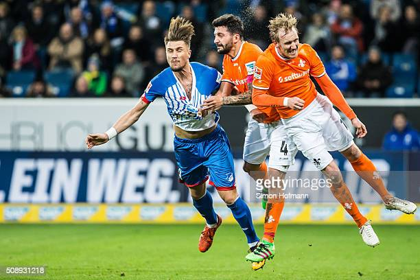 Ermin Bicakcic of Hoffenheim is challenged by Aytac Sulu of Darmstadt during the Bundesliga match between 1899 Hoffenheim and SV Darmstadt 98 at...